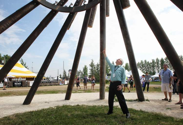 Premier Greg Selinger points jubilantly up at the top of the Festival Tower shortly after the grand opening of the Winnipeg Folk Festival and its new Festival Village. (Mike Deal / Winnipeg Free Press)