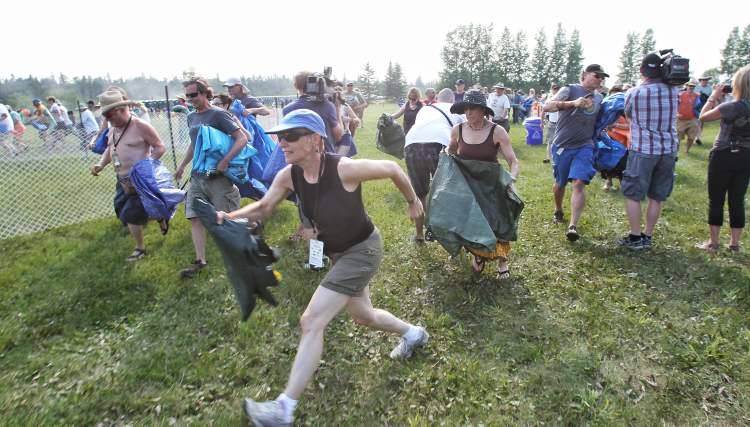 Festival-goers make the traditional run to the main stage, tarps in hand, to stake out a spot.