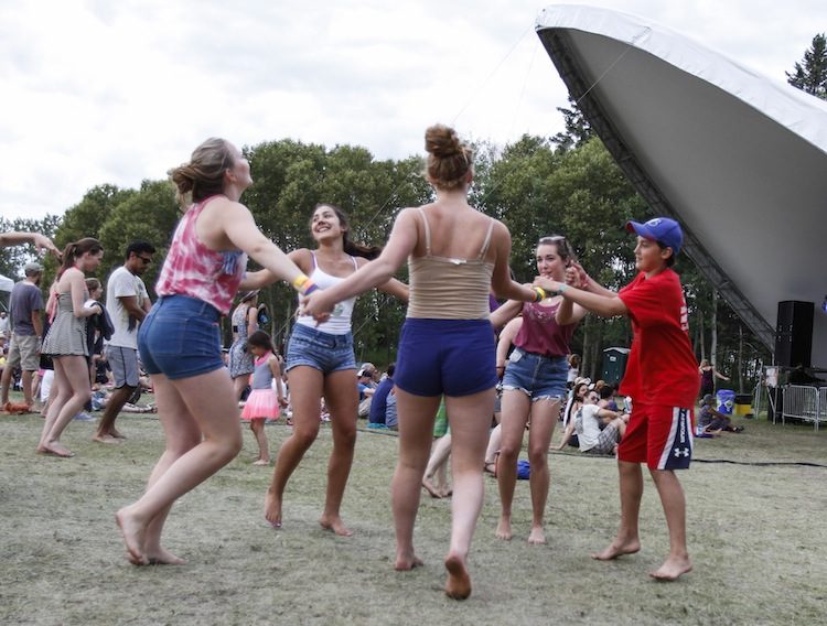 Friends dance together at the Big Blue stage. (JESSICA BURTNICK / WINNIPEG FREE PRESS)