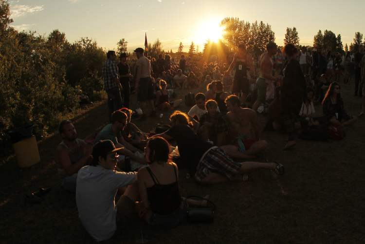 Friends sit in the grass as the sun sets Sunday.