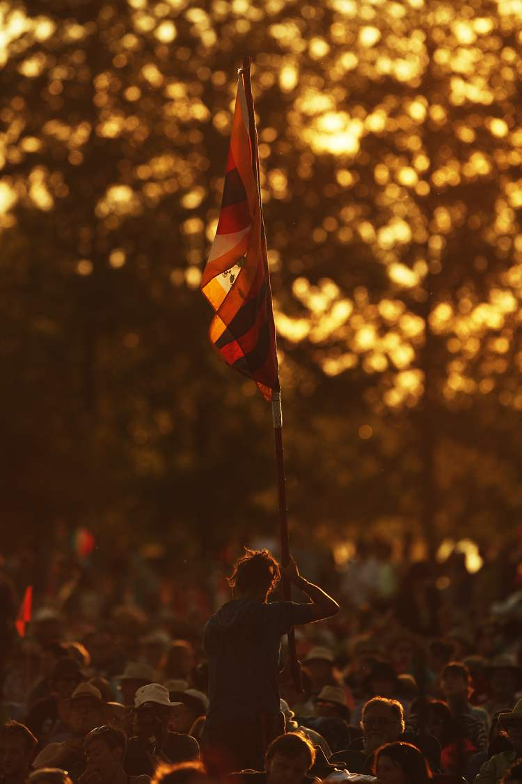 A spectator holds a flag as the sun sets.
