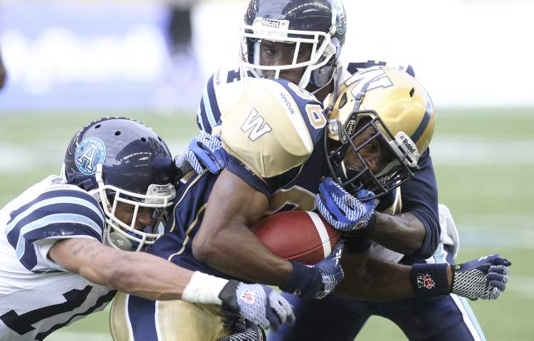 Winnipeg Blue Bombers' Isaac Anderson (86) is brought down by Janzen Jackson (10) and Jamie Robinson (4) i of the Toronto Argonauts in the second quarter (MIKE DEAL / WINNIPEG FREE PRESS)