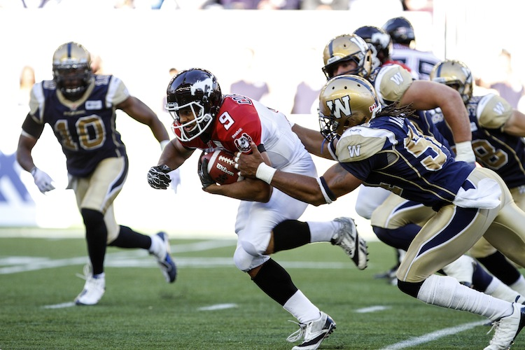 Jon Cornish (#9) of the Calgary Stampeders is tackled by Kenny Mainor (#54) during the first quarter of Friday night's game at Investrs Group Field.