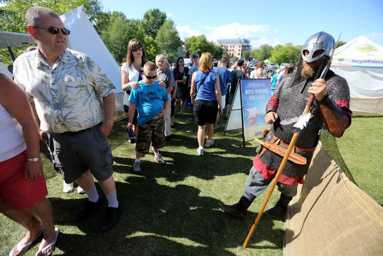A member of Vikings Vinland speaks with visitors to the Viking Village.