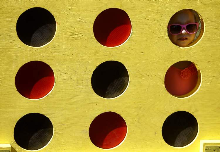 Lola Maier, 2, from Vancouver, peeks through an over-sized game of Connect Four at Islendingadagurinn.
