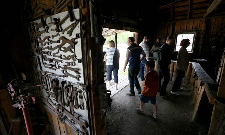 Visitors take a look at the blacksmith shop. (TREVOR HAGAN / WINNIPEG FREE PRESS)