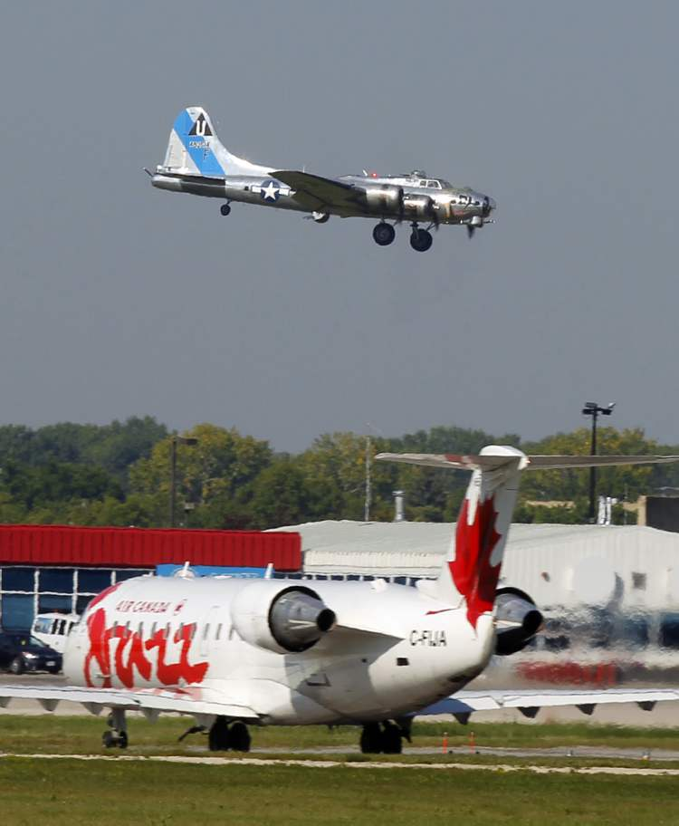An Air Canada Jazz flight sits in the foreground as Sentimental Journey approaches the runway. (BORIS MINKEVICH / WINNIPEG FREE PRESS)
