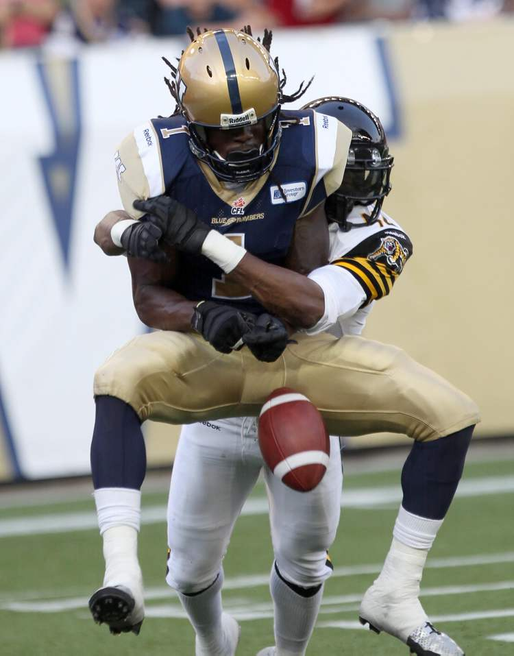 Winnipeg Blue Bombers' Kito Poblah is grabbed by Hamilton Tiger-Cats' Raymond Brown in the end zone during play Friday night. Hamilton was called on this play and set up a touchdown for the Bombers on the next play.