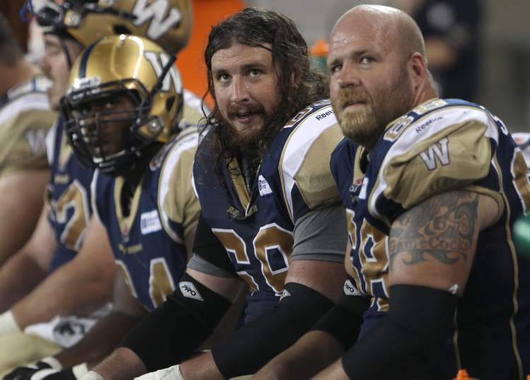 Winnipeg Blue Bombers Glenn January (centre) and teammate Justin Sorensen sit dejected on the bench during the last minute of the fourth quarter. (JOE BRYKSA / WINNIPEG FREE PRESS)