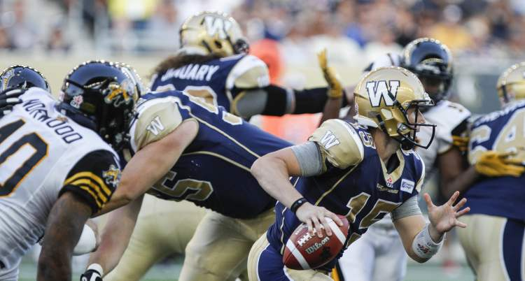 Winnipeg Blue Bombers quarterback Max Hall dashes with the ball.
