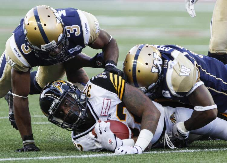 Cauchy Muamba (left) and Brandon Stewart bring down C.J. Gable of the Hamilton Tiger-Cats. (JESSICA BURTNICK / WINNIPEG FREE PRESS)