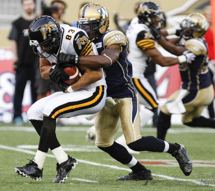 Winnipeg Blue Bombers Cauchy Muamba tackles Andy Fantuz of the Hamilton Tiger-Cats. (JESSICA BURTNICK / WINNIPEG FREE PRESS)