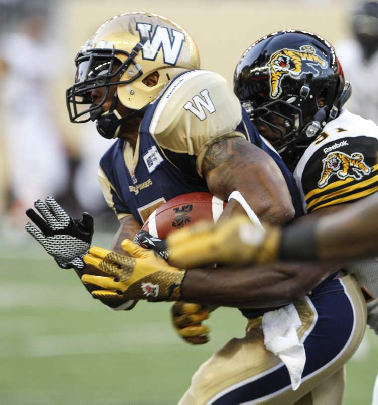 Chad Simpson is tackled by Hamilton Tiger-Cats JT Gilmore.