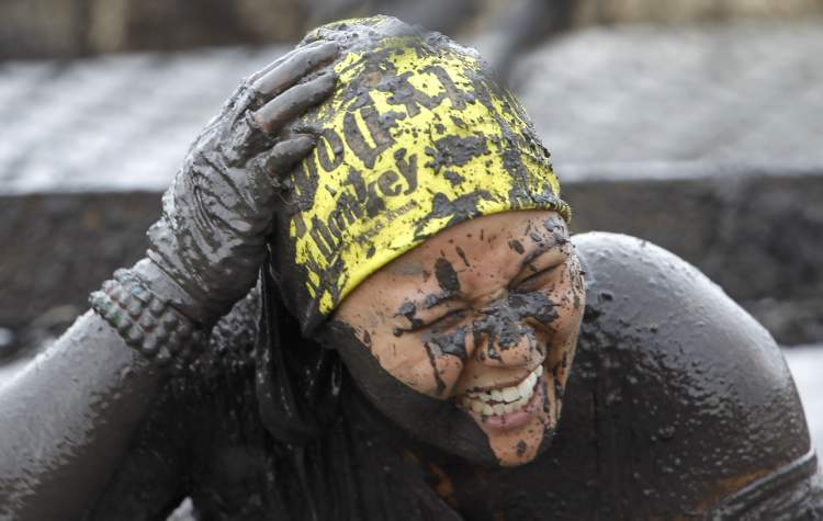 Lillian Mendoza emerges from a pit full of mud near the finish line of the Dirty Donkey Run.