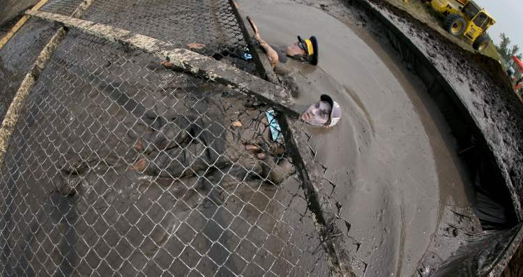 Participants submerge themselves in mud to slide under an obstacle.