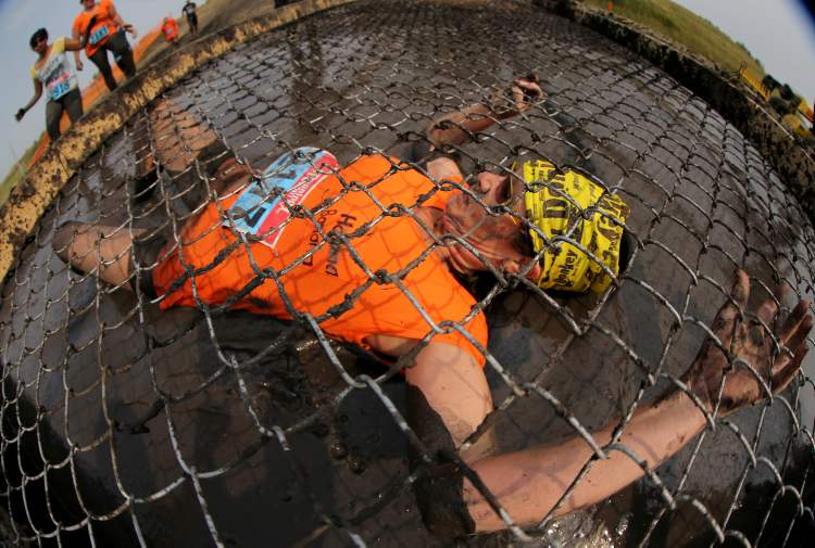 A participant clings to an obstacle while slithering under. (TREVOR HAGAN / WINNIPEG FREE PRESS)