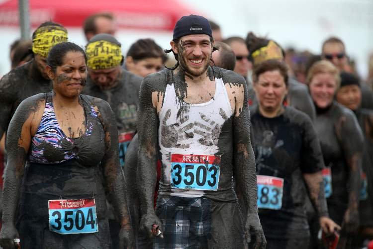 Participants wait to be hosed off after completing the Dirty Donkey Run. (TREVOR HAGAN / WINNIPEG FREE PRESS)