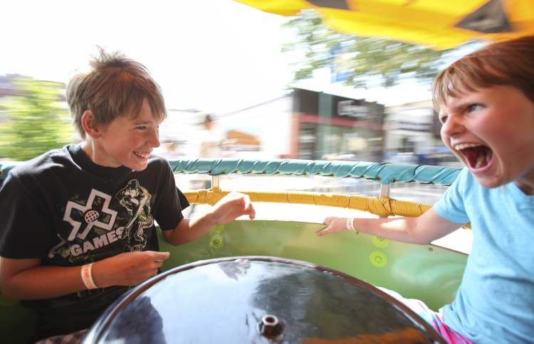 Friends Emma Duncan (right) and Braeden Dance take a spin on a teacup-type ride on the midway.
