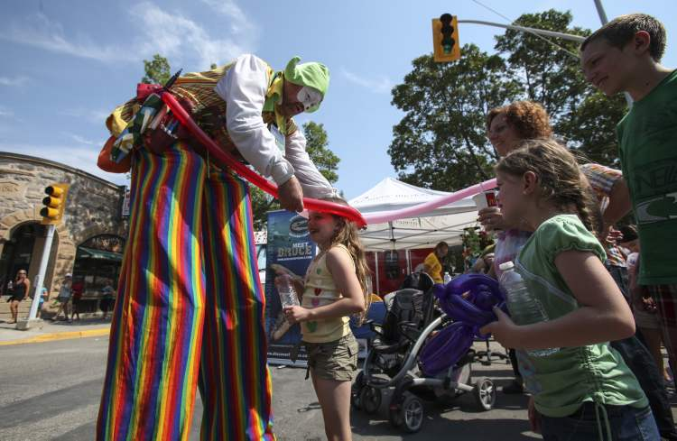 Balloon critters are made to order at the Morden Corn and Apple Festival. Danae Dick, 8, is fitted with a balloon hat while identical twin sister Kaitlyn (right) and others watch. (JESSICA BURTNICK / WINNIPEG FREE PRESS)