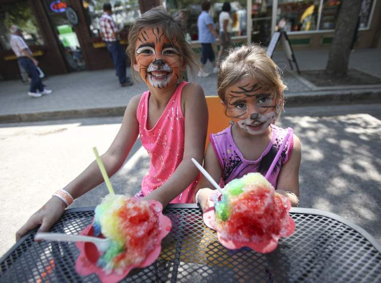 There's more than just corn to be had. Eight-year-old Jaydyn Gilmore (left) and her sister Kalley, 6, make a purr-fect pair with matching tiger face paint and rainbow ice confections at the festival.
