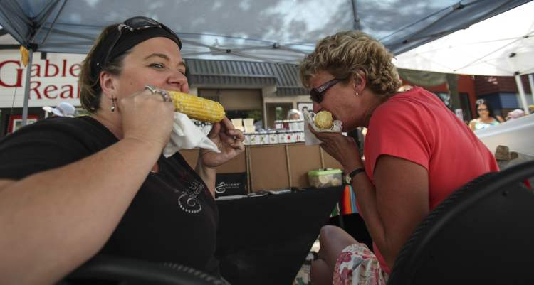 Allison Delaurier (left) and Jannine Alderson sneak a bite to eat behind their wall of Epicure spices for sale at the Festival. (JESSICA BURTNICK / WINNIPEG FREE PRESS)
