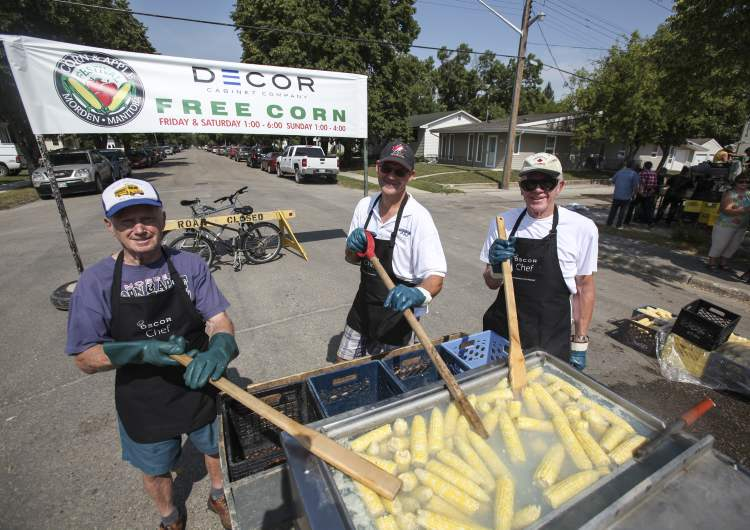 Bill Zacharias (left), who has taken part in the festival for the past 19 years, stirs up some boiling hot corn with Rick Rempel (centre) and Jack Zacharias (right). (JESSICA BURTNICK / WINNIPEG FREE PRESS)