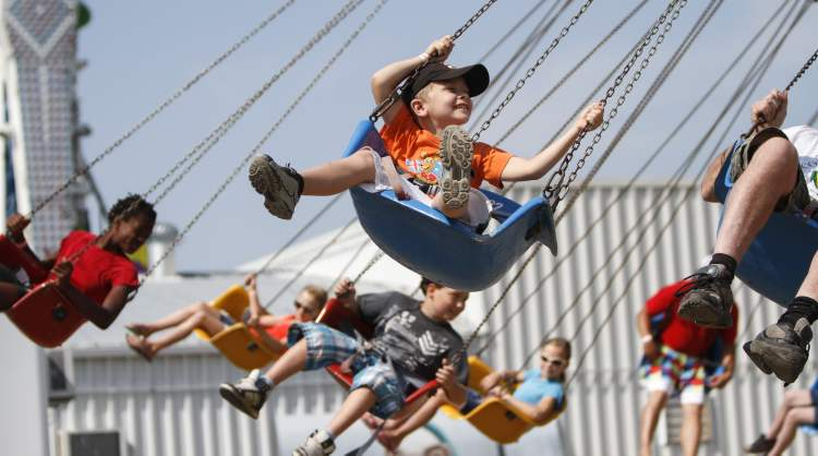 Six-year-old Austin West of Calgary is all smiles on the midway's swing ride. (JESSICA BURTNICK / WINNIPEG FREE PRESS)