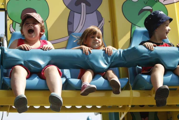 (Left to right) Cousins Livian Zacharias, 6, Paige Barkley, 2, and Connor Zacharias, 5, are mostly smiles on a midway ride. (JESSICA BURTNICK / WINNIPEG FREE PRESS)