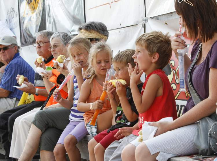 Four-year-old Trey Waite of Morden chows down on corn, while some of his friends enjoy frozen treats. (JESSICA BURTNICK / WINNIPEG FREE PRESS)