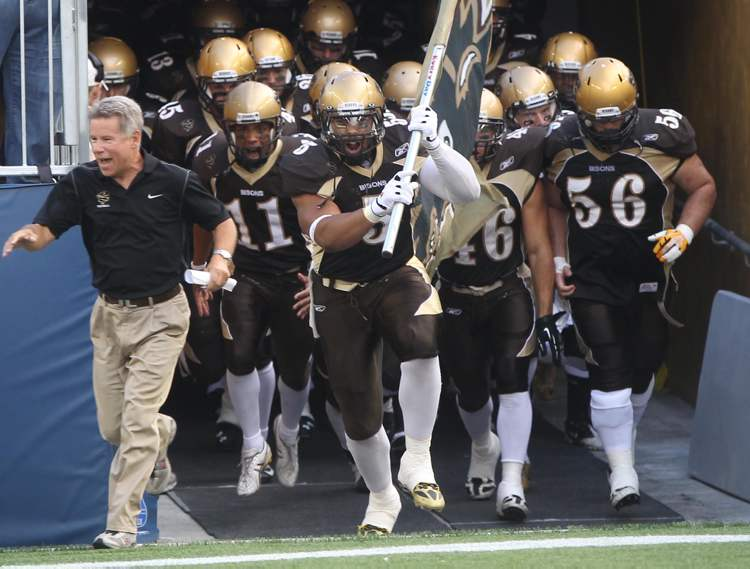 Bisons coach Brian Dobie (left) leads his team onto the field at Investors Group Field. (JOE BRYKSA / WINNIPEG FREE PRESS)