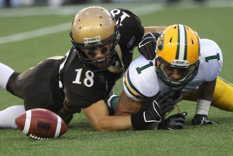 Manitoba Bisons Alex Vitt (left) gets into position to grab a fumble in the first quarter from University of Alberta Golden Bears Tylor Henry.