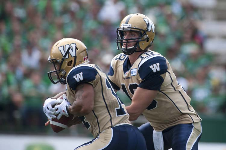 Winnipeg Blue Bombers quarterback Justin Goltz hands the ball of to slotback Aaron Woods first half against the Saskatchewan Roughriders in CFL football action in Regina, Sask., Sunday, September 1, 2013. THE CANADIAN PRESS/Liam Richards