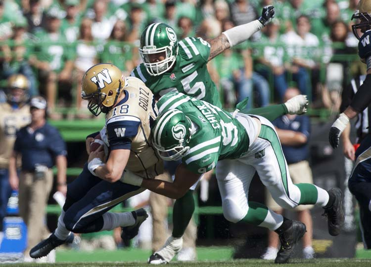 Saskatchewan Roughriders defensive end John Chick sacks Winnipeg Blue Bombers quarterback Justin Goltz during the first half of CFL football action in Regina, Sask., Sunday, September 1, 2013. THE CANADIAN PRESS/Liam Richards