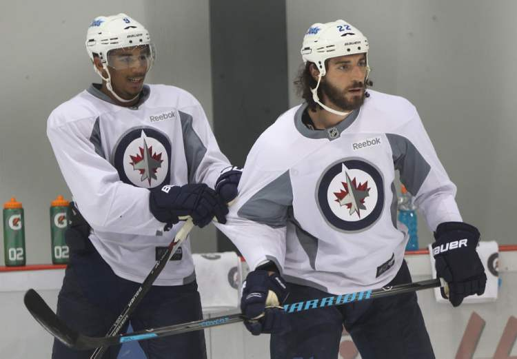 Evander Kane, left holds onto Chris Thorburn.
