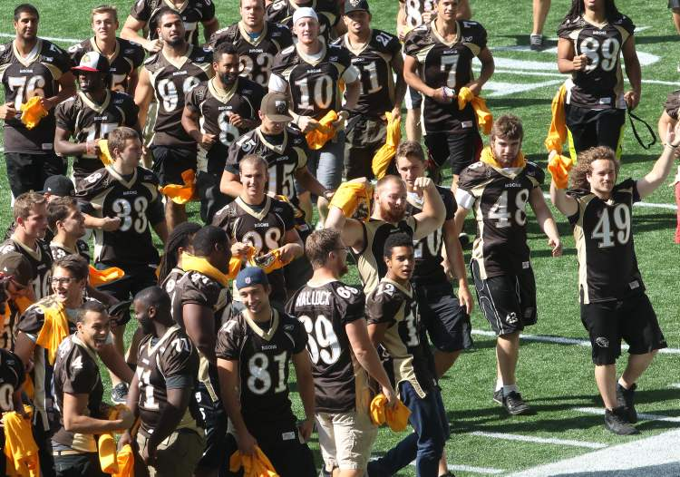 University of Manitoba pep rally at Investors Group Field Tuesday afternoon. University of Manitoba mens football team runs on field. (JOE BRYKSA / WINNIPEG FREE PRESS)