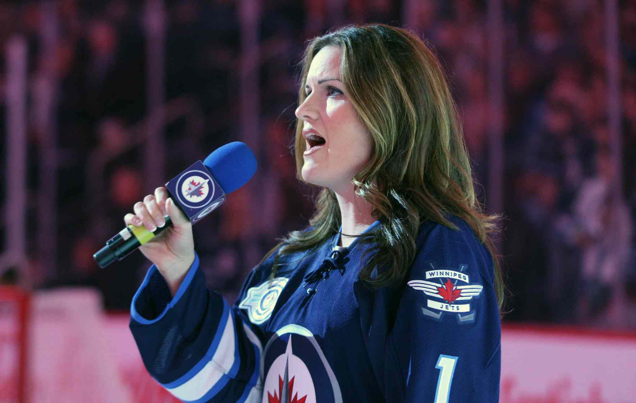 Wearing her personalized Jets home jersey, Stacey Nattrass belts out the national anthem before a pre-season NHL game at the MTS Centre earlier this year.