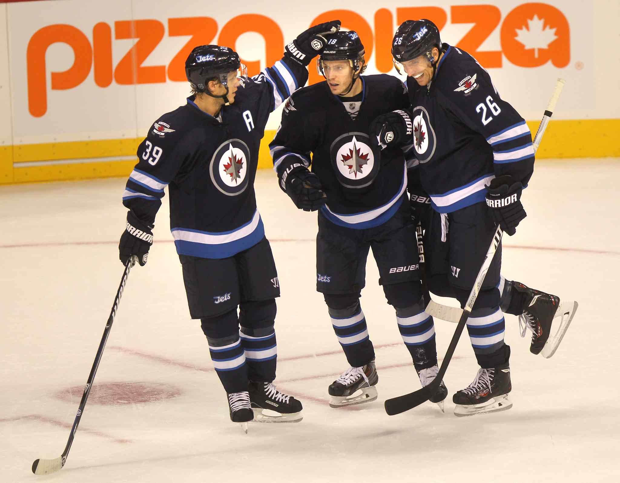 Winnipeg Jets Tobias Enstrom (left) and Blake Wheeler (right) congratulate Bryan Little on his first-period goal.