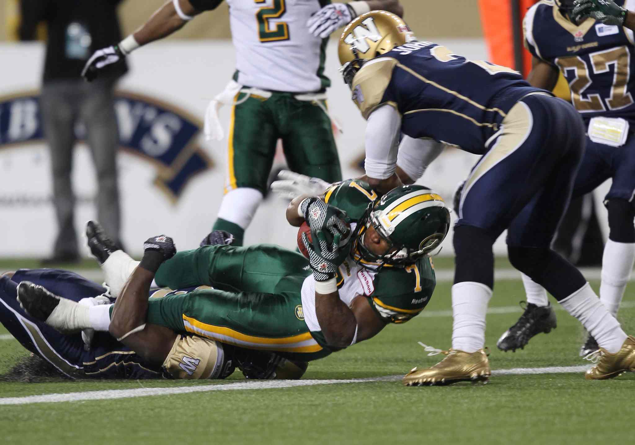 Winnipeg Blue Bombers Cauchy Muamba (bottom) and Jovon Johnson try unsuccessfully to hold back Edmonton Eskimos' Hugh Charles as he pounds in for a touchdown in overtime. the Esks added a two-point convert.