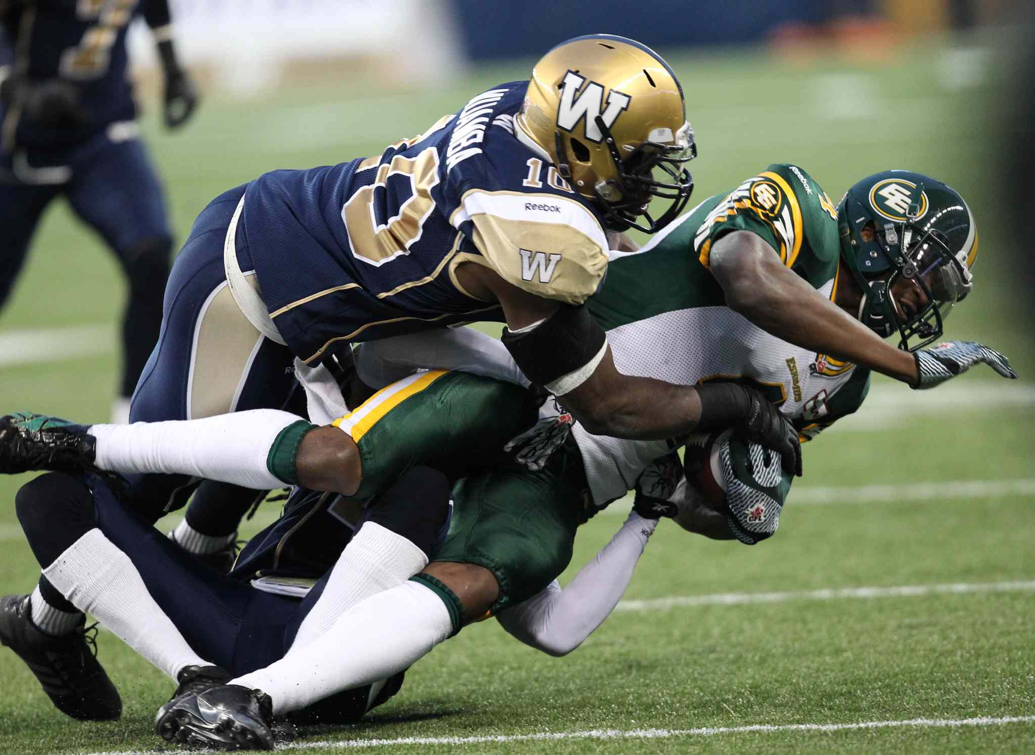Winnipeg Blue Bombers Henoc Muamba tackles Adarius Bowman of the Edmonton Eskimos during the first half.