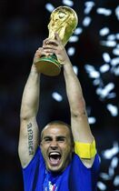 FILE - In this Sunday, July 9, 2006 file photo Fabio Cannavaro holds aloft the World Cup trophy after the final of the soccer World Cup between Italy and France in the Olympic Stadium in Berlin. Italy's winning World Cup captain Fabio Cannavaro is reportedly under investigation for tax evasion. Local media report Wednesday Oct. 22, 2014 that nearly one million euros (more than $1 million) worth of goods linked to Cannavaro were sequestered by tax police in his hometown of Naples. Without providing details, Italy's tax agency confirmed the reports. A statement from Cannavaro's lawyers said that the inquiry involves a company owned only by the player's wife, adding that the couple is convinced it did no wrong. (AP Photo/Jasper Juinen, file)