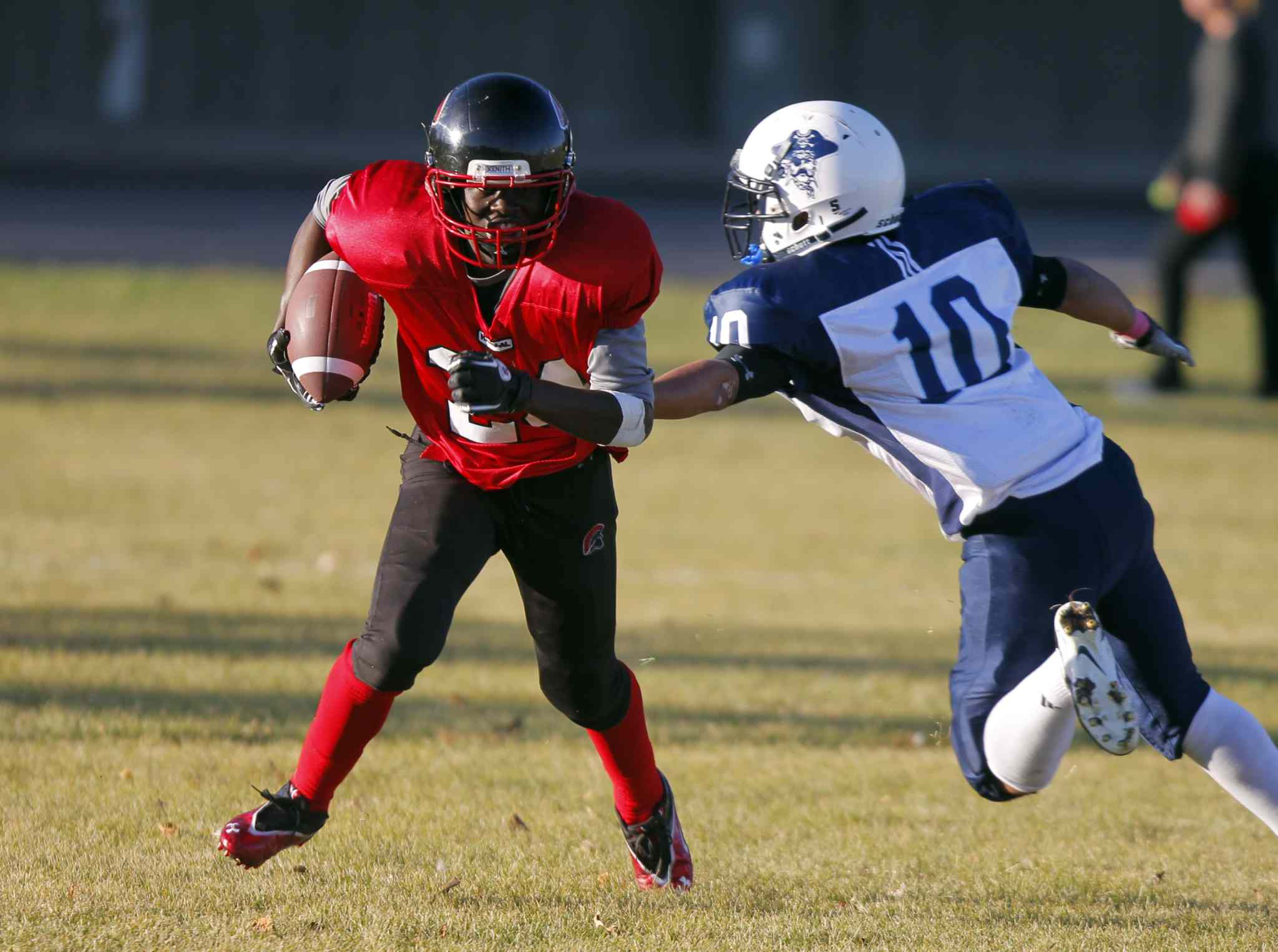 Ibrahim Bangura of the Spartans (left) tries to break past Pirates running back Ben Lowe.