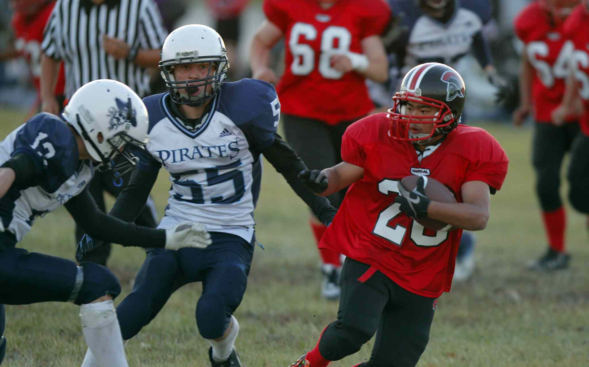 Ivan Jaque of the Spartans (right) tries to evade Ron Almonte (left) and Max Zimberg of the Grant Park Pirates.