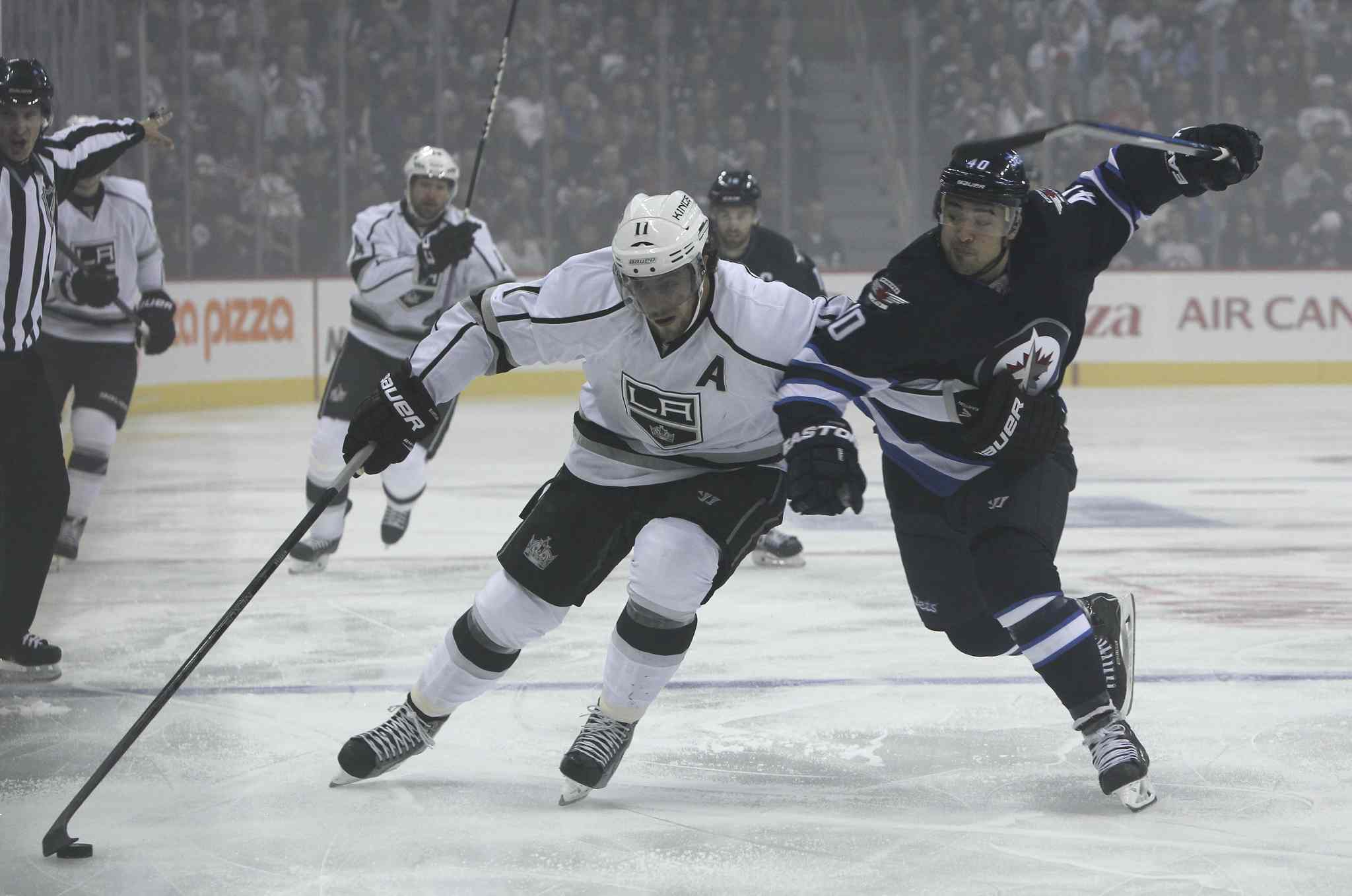 Devin Setoguchi (40) of the Winnipeg Jets tries to slow down Los Angeles Kings' Anze Kopitar (11) in the first period of Friday night's home opener at the MTS Centre.