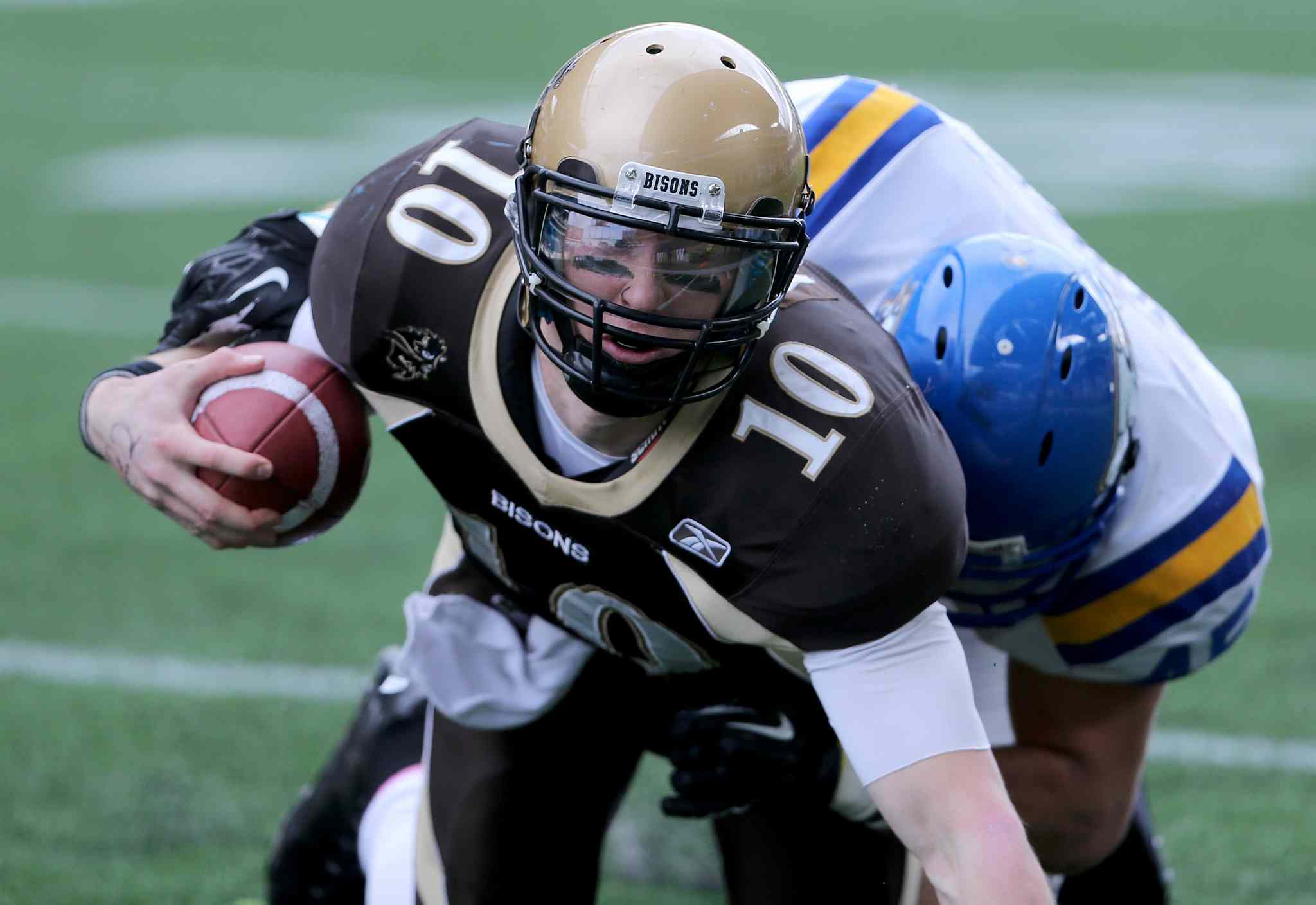 UBC Thunderbirds' Riley Jones (right) tackles University of Manitoba Bisons quarterback Jordan Yantz during their game at Investors Group Field, Saturday.