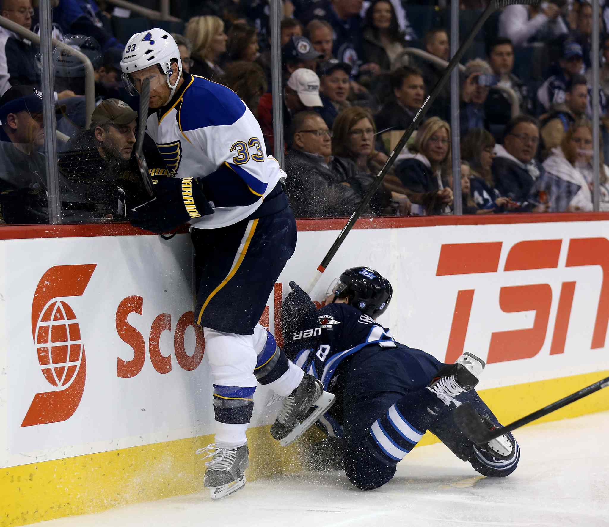Jordan Leopold of the St. Louis Blues plays the puck as Jacob Trouba goes crashing into the boards during the second period.