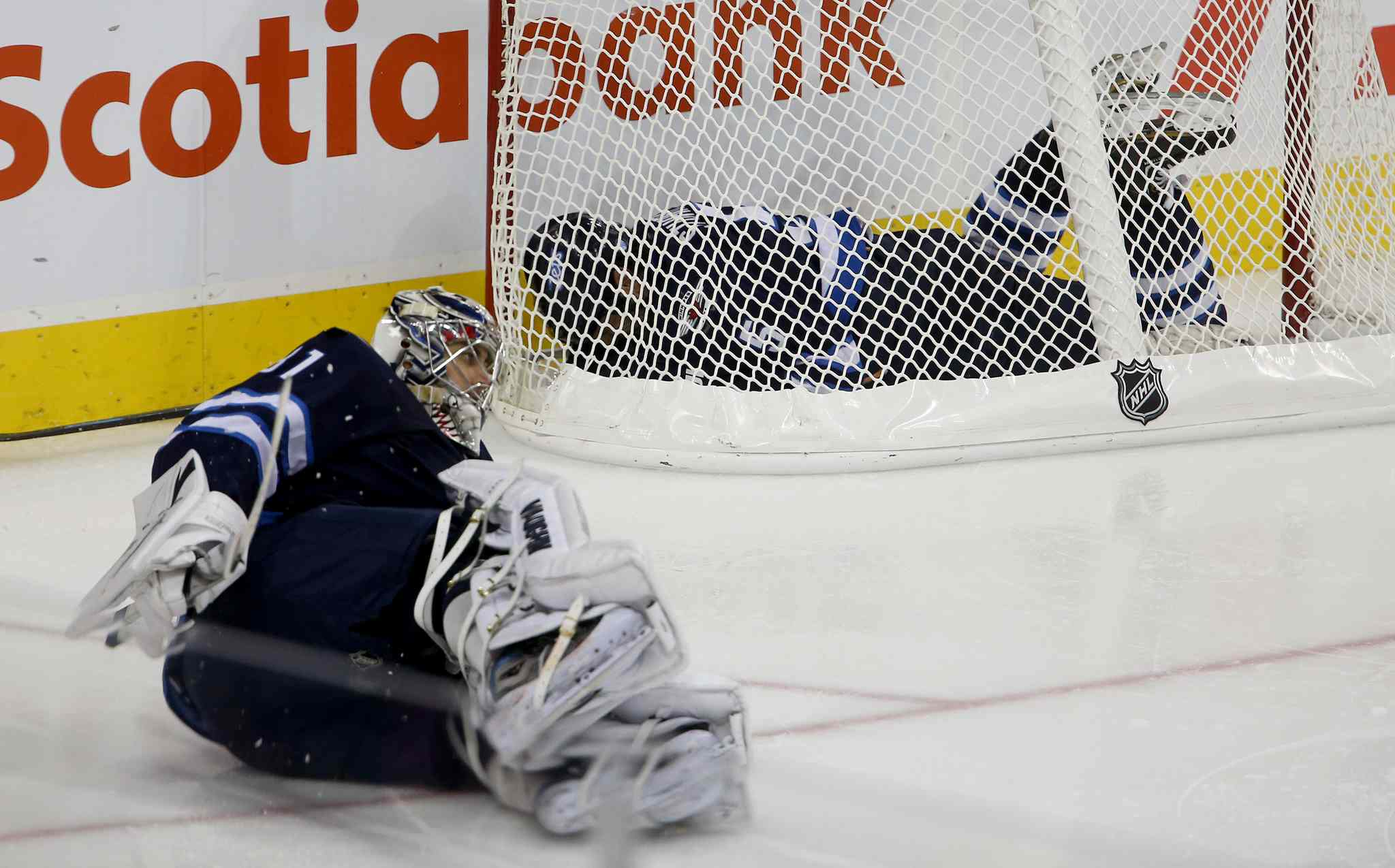 Winnipeg Jets' Mark Stuart ends up in the Jets' net after colliding with goaltender Ondrej Pavelec during the third period.