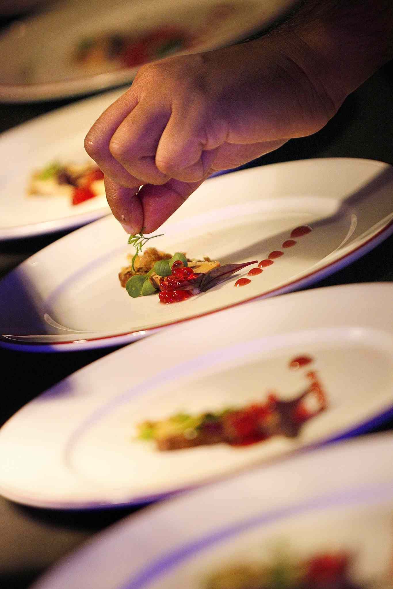 A chef puts the finishing touches on an appetizer dish.