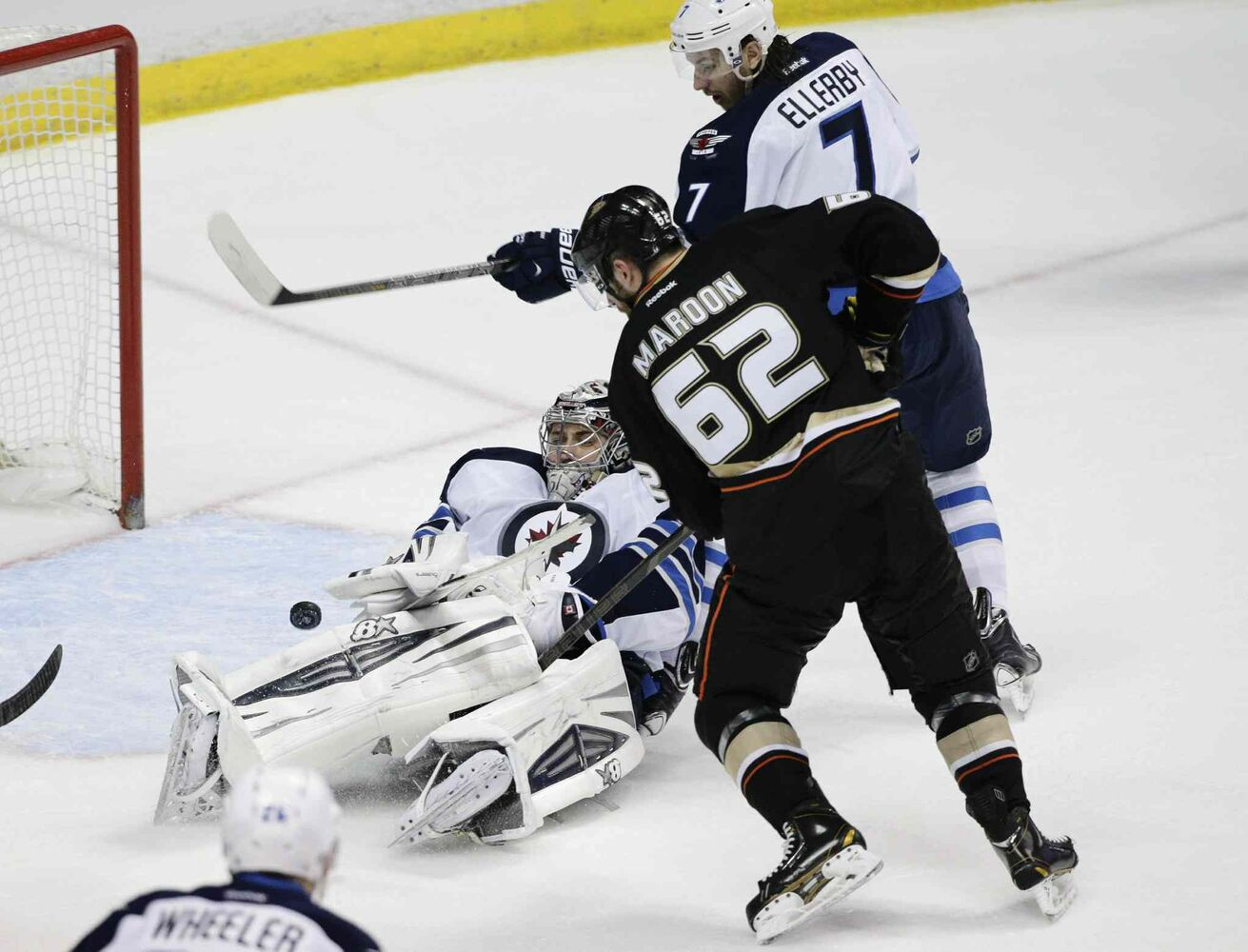 Winnipeg Jets' goalie Ondrej Pavelec, left, makes a save as Anaheim Ducks' Patrick Maroon and Winnipeg Jets' Keaton Ellerby, top, watch during the second period in Anaheim Tuesday. (Jae C. Hong / The Associated Press)