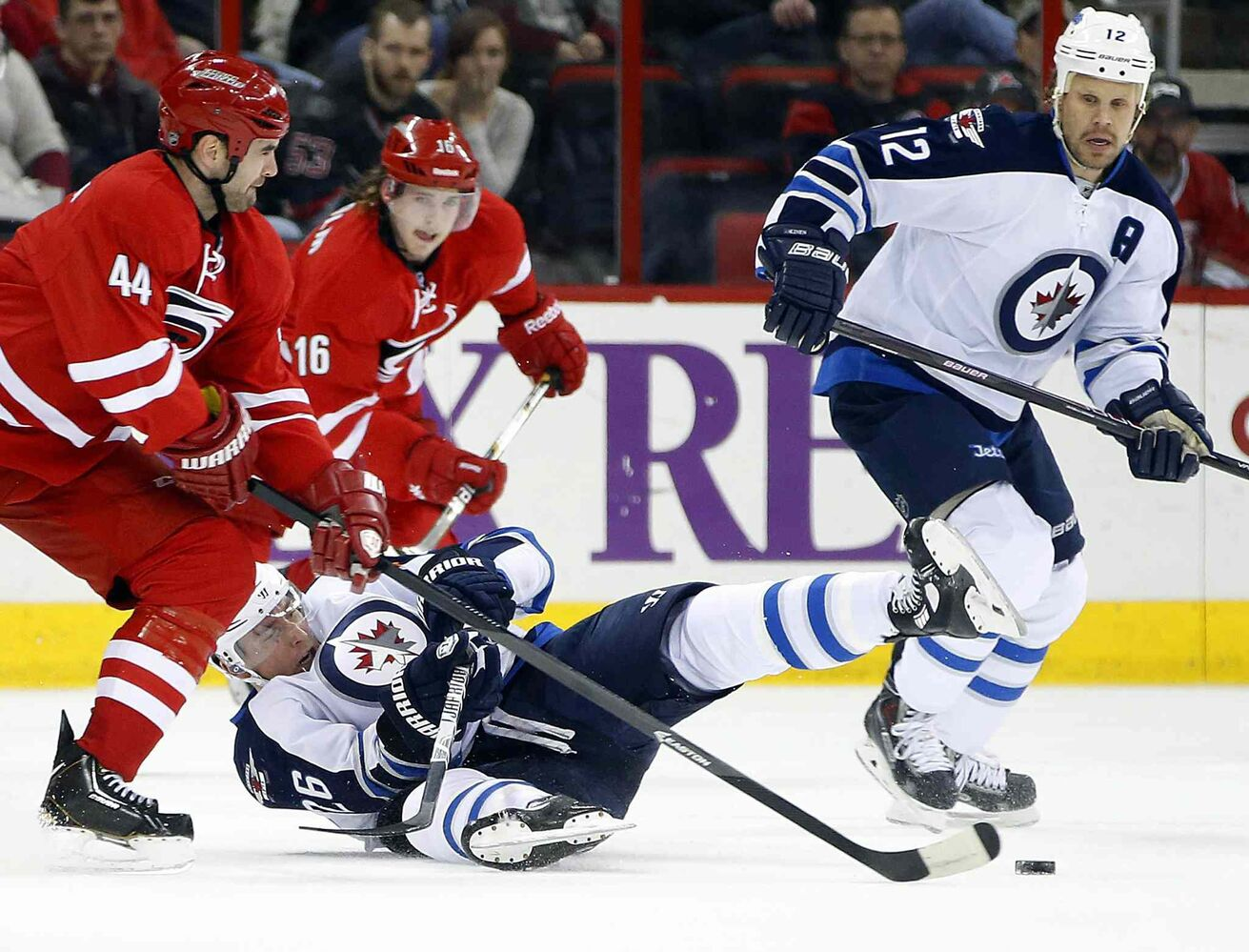 Carolina Hurricanes' Jay Harrison (44) takes Winnipeg Jets' Blake Wheeler (26) off the puck with Olli Jokinen (12) of Finland, during the first period of an NHL hockey game in Raleigh, N.C. on Tuesday.