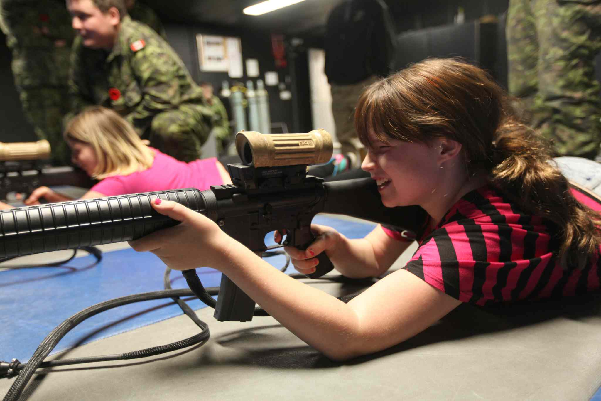 Megan Sawka (front) and her friend Darby Riguidel learn how to shoot an air gun on Saturday, with help from Captain Riguidel and other staff at Minto Armoury during their open house.